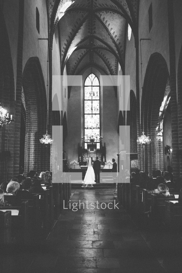 bride and groom exchanging vows in a church
