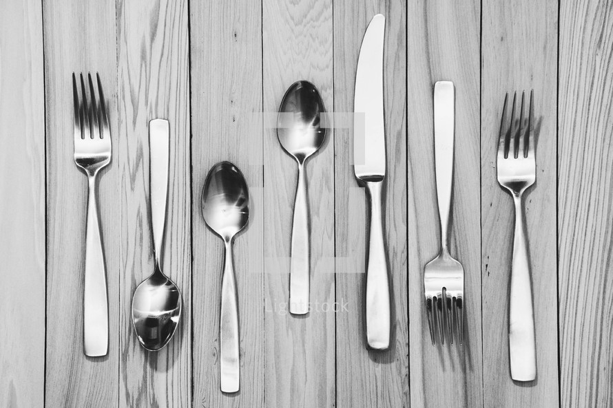 fork, knives, spoons on a wood floor