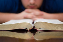 man in prayer in front of a Bible at a Bible study