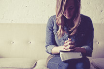 woman sitting on a couch with her hands in prayer held over a Bible.