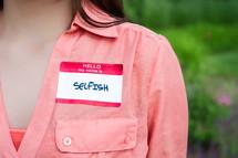 woman wearing a name tag - selfish