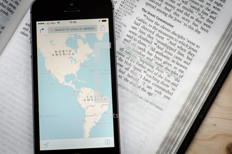 A phone with a world map showing North and South America sitting on a bible open to the great commission