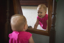 A baby girl looks at herself in the mirror.