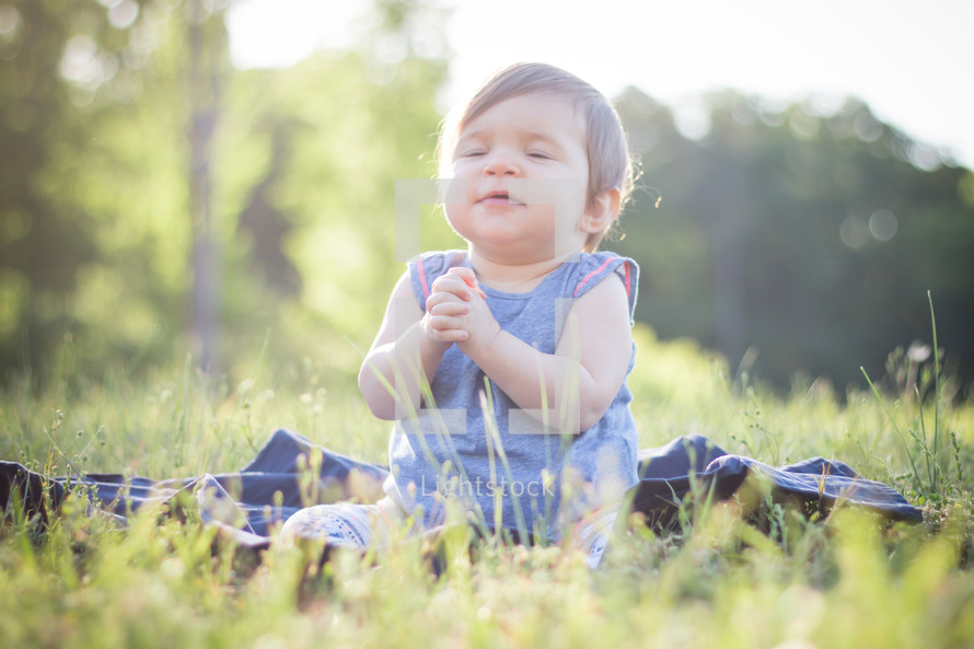a toddler girl sitting in grass clapping her hands