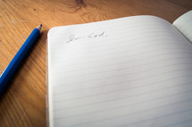 An open notebook with the words 'dear God' written, laying next to a blue pencil on a wooden desk