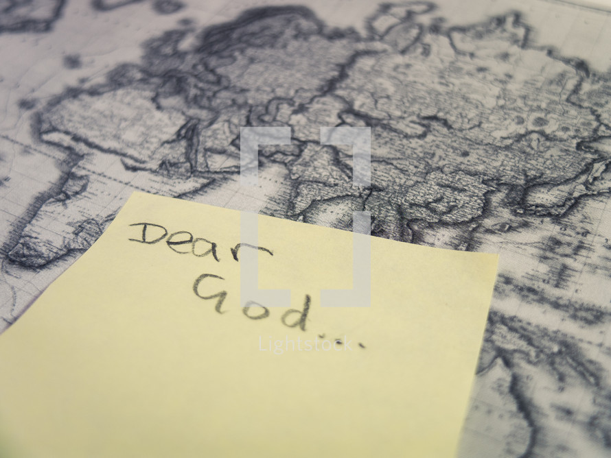 A yellow post-it sticky note with the handwritten words 'dear God' stuck to an antique style world map.