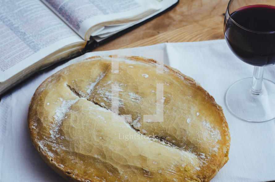 A loaf of bread and glass of wine on a table with an open bible