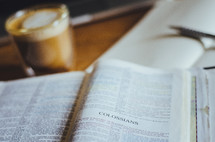 A coffee, notebook and bible open to Colossians on a table.