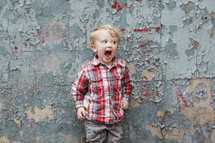 boy child yelling in front of a wall with peeling paint