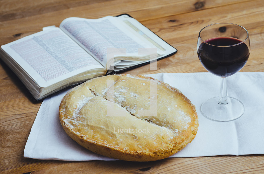 An open bible, loaf of bread and glass of wine on a table