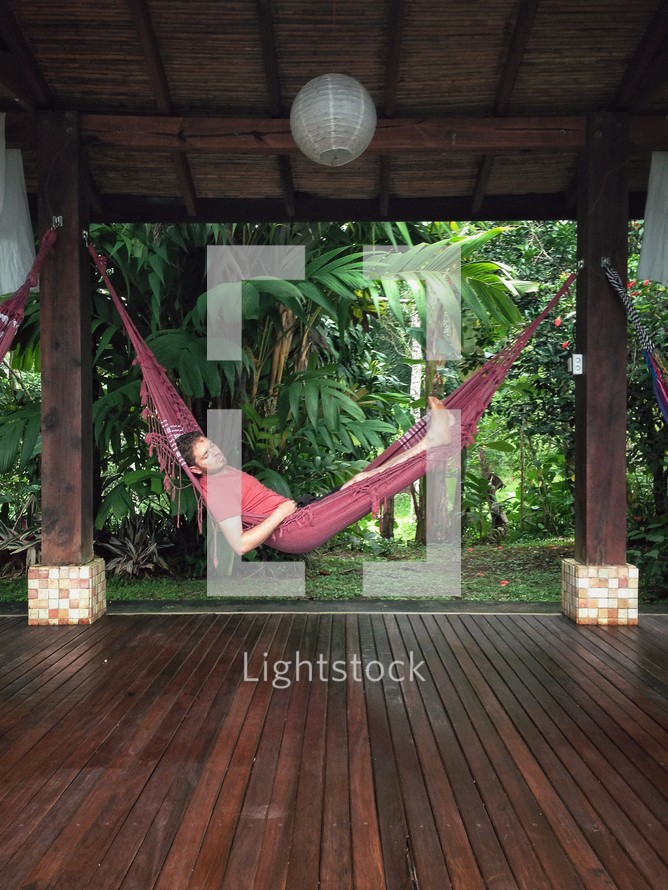 A man resting in a hammock.