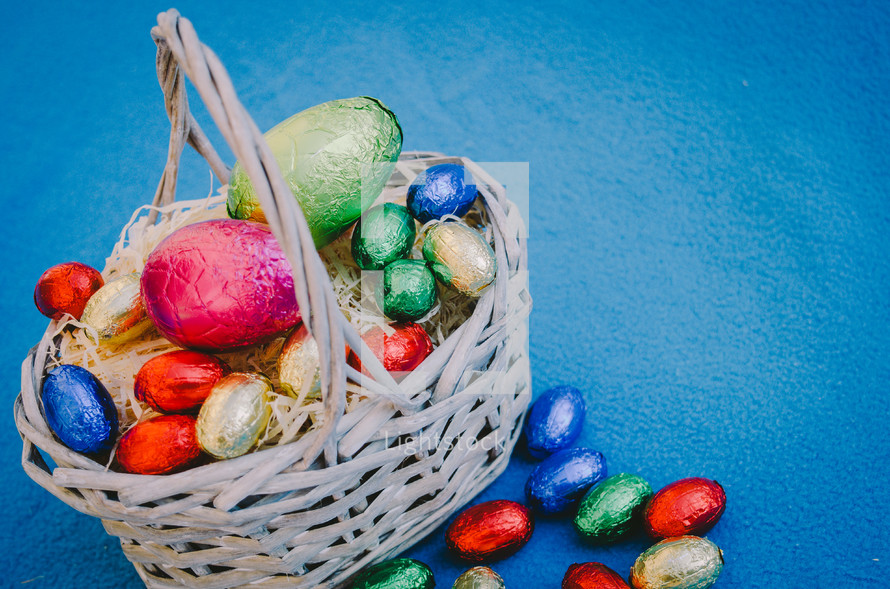 Colored easter eggs in a wicker basket on a blue background