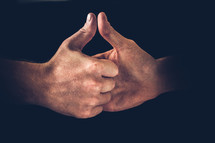 Two hands engaging in Thumb War