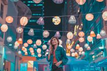 woman standing under paper lanterns