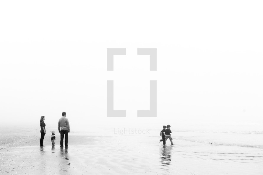 family standing on a beach