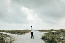 a young man walking over sand dunes