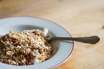 A bowl of museli / granola with a spoon on a wooden table