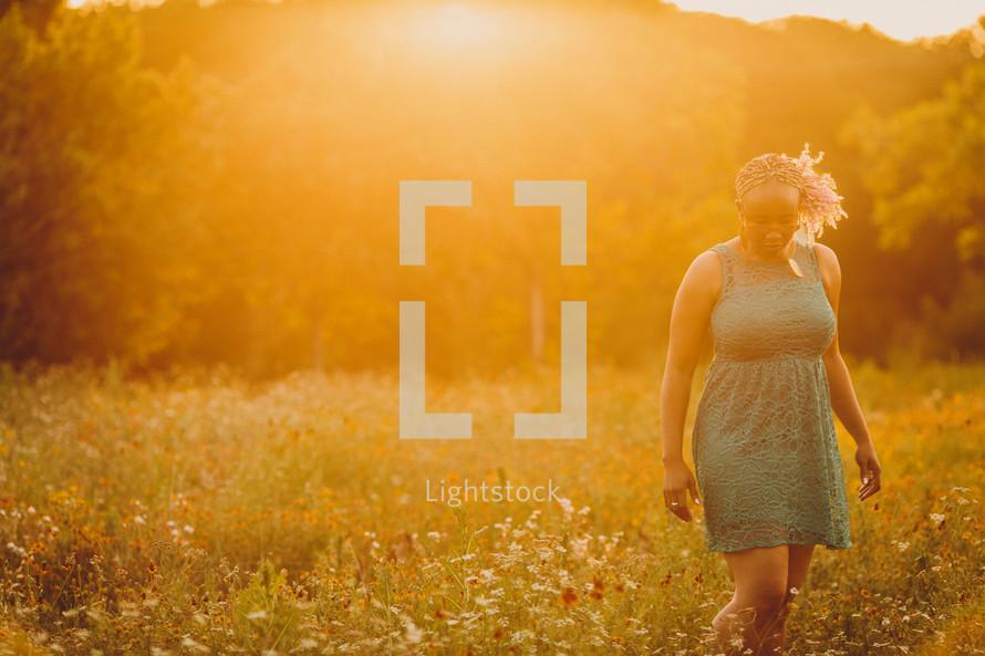 African-American woman walking outdoors in a field of wildflowers under intense sunlight