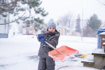 a boy child shoveling snow