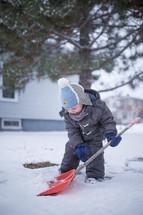a boy child shoveling snow