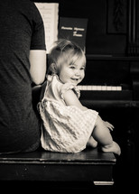 Baby girl listens and smiles while dad plays worship music on the piano.