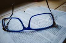 A pair of blue glasses sit atop an open bible.