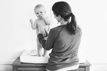 a mother and infant at a changing table