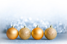 row of gold Christmas ornaments