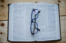 A pair of blue glasses sit atop an open bible