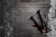 Two bloody nails sit upon an old wooden cross beam