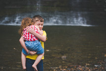 a brother carrying his little sister