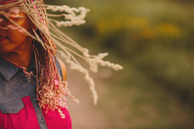 African-American woman with pink and blonde braids twirling her hair outdoors