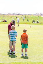 father and sons on the golf course