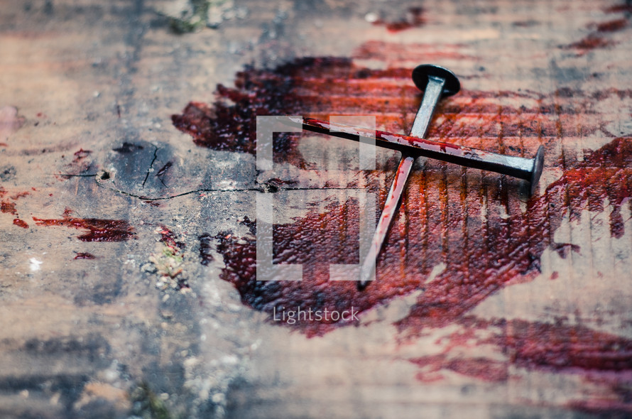 Two bloody nails form a cross on a blood covered wooden beam
