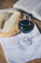 A glass of wine sits on a table next to a loaf of bread and an open bible.