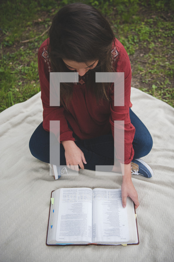 teenage girl sitting on a blanket reading a Bible