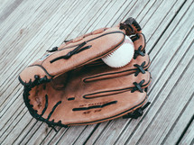 A baseball and glove on a wooden tabletop.