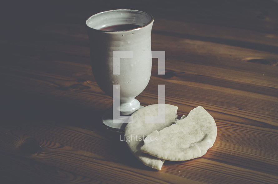 A cup of wine and broken bread on a wooden table.