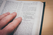 A bible opened to Luke's gospel with fingers pointing to the Lord's prayer
