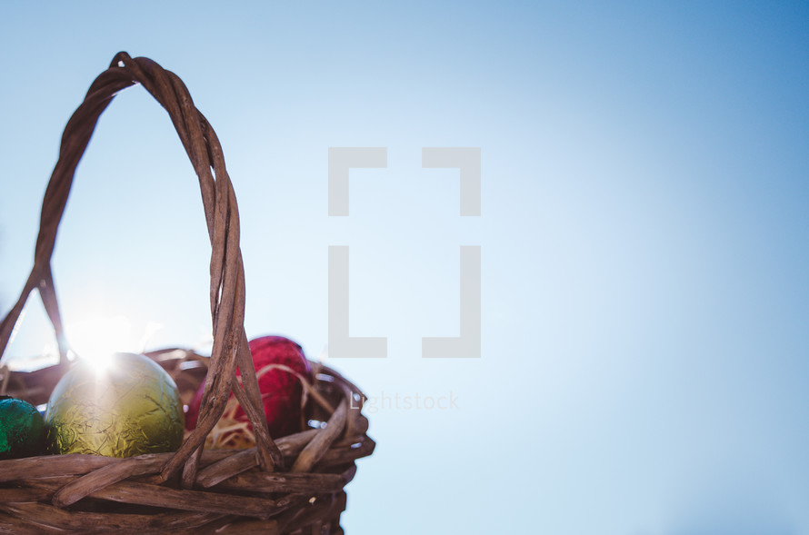 Colored easter eggs in a wicker basket with the sun's rays