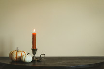 pumpkins and candlestick on a wood table
