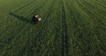 a man squatting down in a field reading a Bible