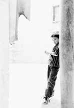 A boy leans against a wall