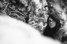 woman in glasses standing in a snow covered forest