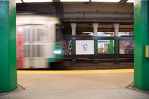 A subway train moving next to the subway platform.