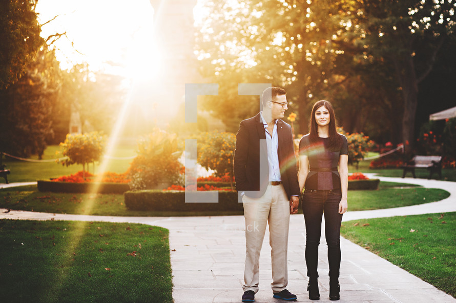 a couple standing on a sidewalk in a garden at sunset