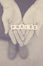 word praise in scrabble pieces in a woman's hands