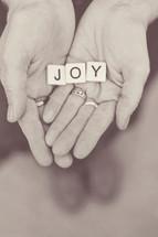word joy in scrabble pieces in a woman's hands