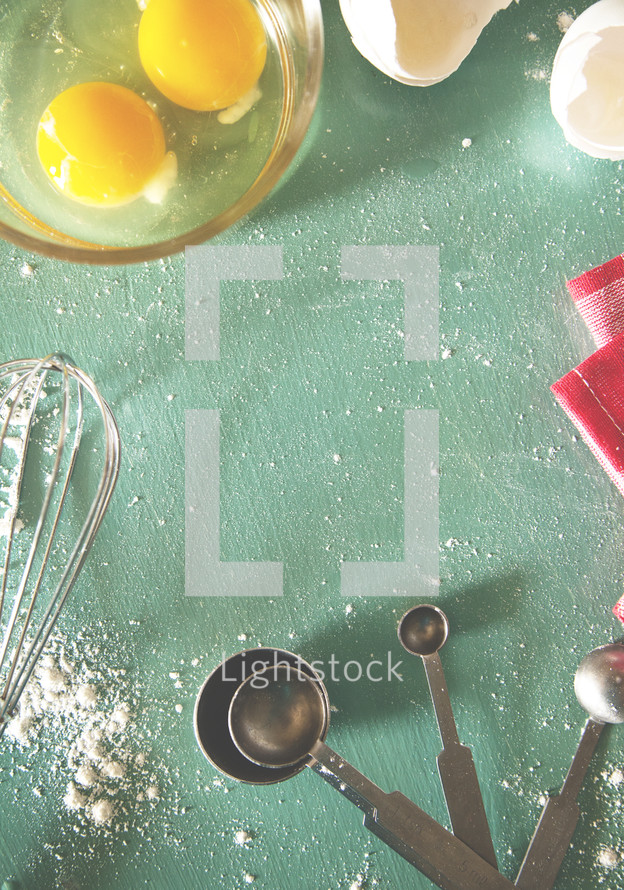 whisk, flour, measuring spoons, cracked eggs, bowl, and towel on a kitchen countertop
