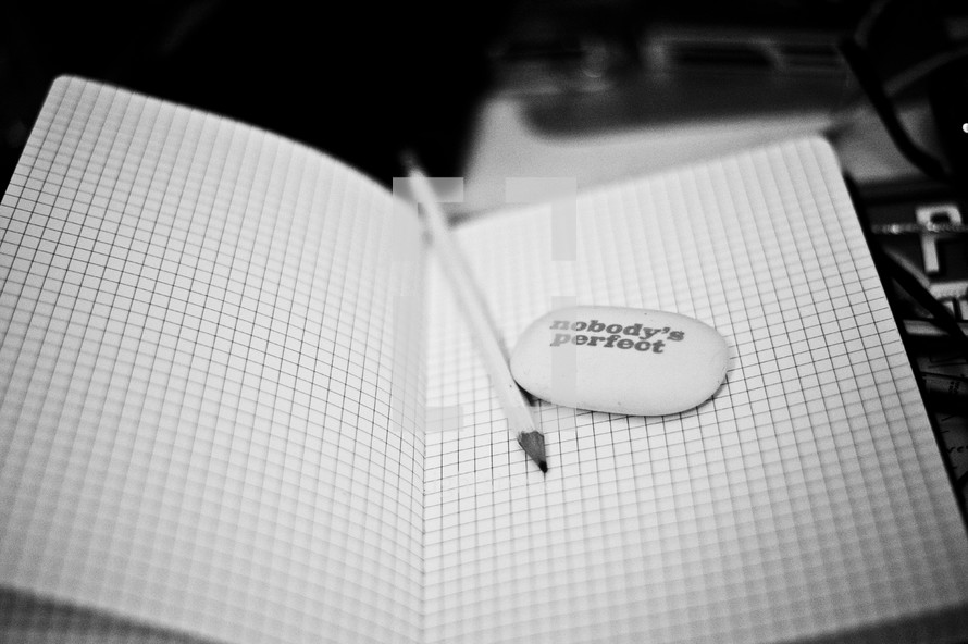 graph paper, a pencil, and a stone with the words NOBODY'S PERFECT